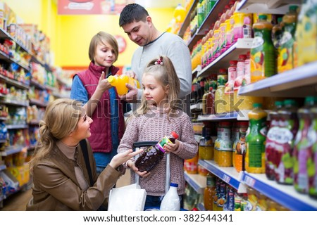 Parents with two kids 7s choosing soda and juice in shop