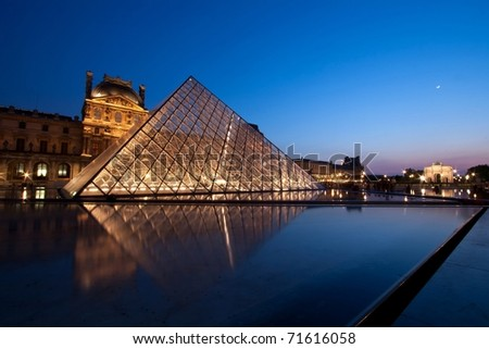 PARIS - APRIL 16: Louvre at dusk during Summer Exhibition.  Louvre is the biggest Museum in Paris displayed over 60,000 square meters of exhibition space. - stock photo