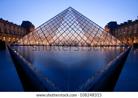 PARIS - APRIL 16: Louvre Pyramid at dusk during the Summer Exhibition April 16, 2010 in Paris. Louvre is the biggest Museum in Paris displayed over 60,000 square meters of exhibition space. - stock photo