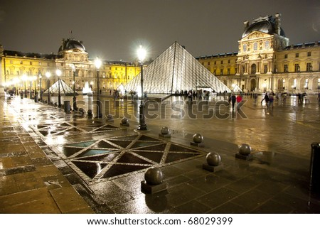 PARIS-APRIL 19: Louvre pyramid at Evening on March 19, 2010 in Paris, France. The Louvre is the biggest Museum in Paris with over 60,000 square meters of exhibition space - stock photo