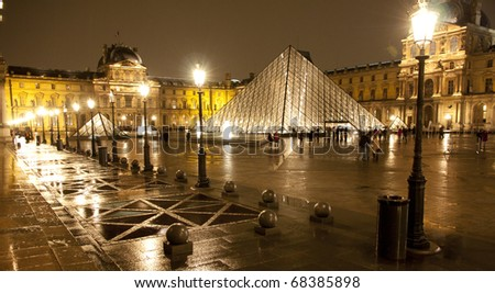 PARIS-APRIL 19: Louvre pyramid at rainy evening on March 19, 2010 in Paris, France. The Louvre is the biggest Museum in Paris with over 60,000 square meters of exhibition space - stock photo
