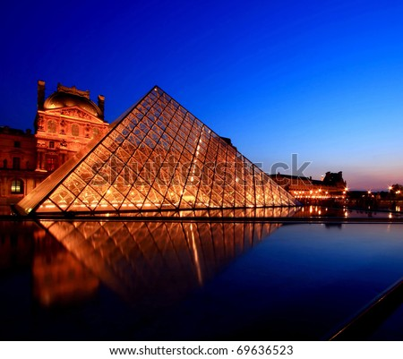 PARIS - APRIL 16: Louvre Pyramid shines at dusk during the Summer Exhibition April 16, 2010 in Paris. Louvre is the biggest Museum in Paris displayed over 60,000 square meters of exhibition space. - stock photo