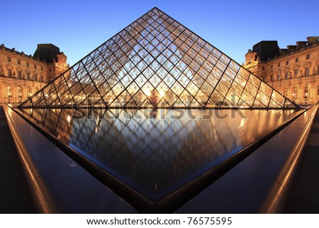 PARIS - APRIL 07: Louvre Pyramid shines at dusk on April 07, 2011 in Paris. Louvre is the biggest Museum in Paris displayed over 60,000 square meters of exhibition space. - stock photo