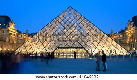 PARIS - APRIL 16: Louvre pyramid shining at dusk during the Summer Exhibition on April 16, 2010 in Paris. Louvre is the biggest Museum in Paris displayed over 60,000 square meters of exhibition space. - stock photo