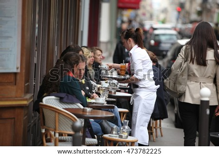PARIS - APRIL 27 : People enjoy eat and drinks in cafe sidewalk in Paris, France on April 27, 2013. Paris is one of the most populated metropolitan areas in Europe