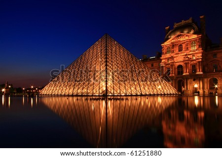 PARIS-APRIL 16: Reflection of Louvre pyramid shines at dusk during the Summer Exhibition April 16, 2010 in Paris.Louvre is the biggest Museum in Paris displayed over 60,000 sqr.m of exhibition space. - stock photo