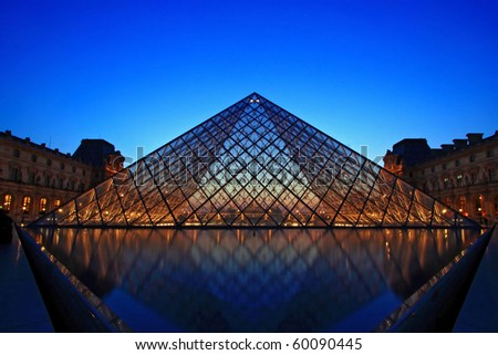 PARIS - APRIL 16: Shining of Louvre pyramid at Evening during the Egyptian Antiquities Summer Exhibition April 16, 2010 in Paris. This is one of the most popular tourist destinations in France. - stock photo