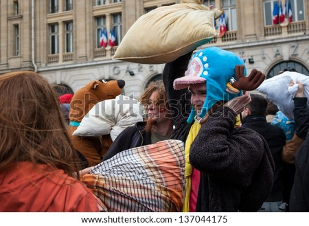 PARIS - APRIL 6: Unidentified people participate in pillow fight at Gare Saint-Lazare square on April 6, 2013 in Paris, France. This year the International Pillow Fight Day was celebrated  on April 6.