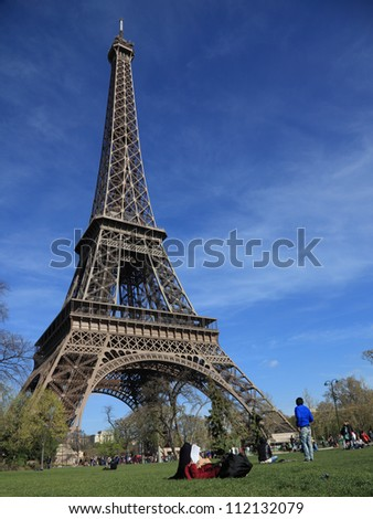 PARIS- APRIL 1:Unidentified student reading at the base of the Eiffel Tower on April 1 2012 in Paris,France.The Eiffel tower is the most visited monument of France with over 6 million visitors a year. - stock photo