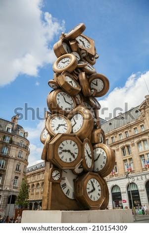 PARIS - AUGUST 10: clock sculpture in front of the Gare St. Lazare with unidentified people on August 10, 2014 in Paris. L heure de tous -1985-, sculpture by Arman -Armand Pierre Fernandez, 1928-2005- - stock photo