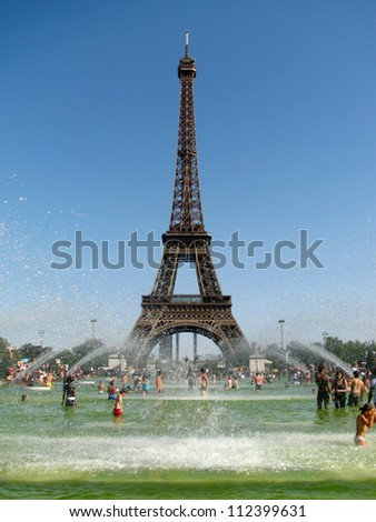PARIS - AUGUST 18: the majestic Eiffel Tower on August 18, 2012 in Paris, France. A record heatwave in Paris, 38° Celsius. A crowd of people is cooled in the fountains in front of the Eiffel Tower. - stock photo