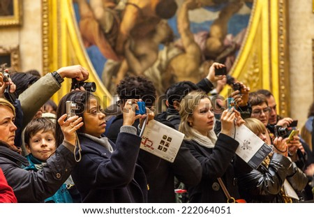 PARIS - DEC 19:Crowd of unidentified people use various digital devices to photograph paintings in Louvre Museum on 19 December 2011 in Paris.Louvre is the most visited museum worldwide - stock photo