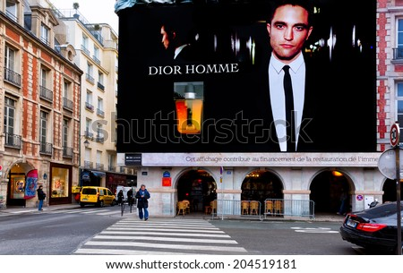 PARIS-DEC 23,2013: Dior Homme perfume billboard dominates a corner at Place des Vosges, the oldest square in Paris. Dior calls the scent the distinguished mark of a man with uninhibited elegance. - stock photo
