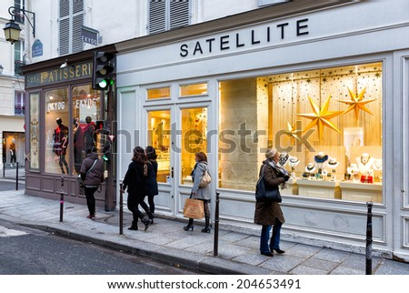 PARIS-DEC 23, 2013: Holiday shoppers on a Paris street in the Marais, the historic district in the heart of the city, with store windows dressed up for Christmas. - stock photo
