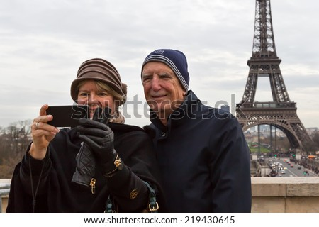 PARIS-DEC 31, 2013: Senior tourists take a selfie with the Eiffel Tower in the background. This spot on the Esplanade du Trocadero has the best view of the iconic tower and attracts thousands daily. - stock photo