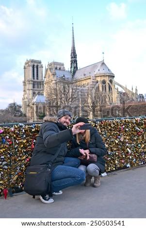 PARIS - DEC 30: tourists making photo near the Notre-Dame Cathedral (aka Cathedral Notre Dame de Paris) on December 30, 2014 in Paris, France. It was build during 1163-1325. - stock photo