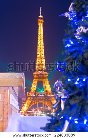 PARIS - DECEMBER 16, 2013: A Christmas tree the Trocadero gardens. The Eiffel Tower in the background displays a written tribute to Nelson Mandela who died on December 5th that year. Focus is on tree. - stock photo
