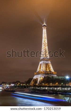 PARIS - DECEMBER 27: Eiffel Tower and river Seine at night on December 27, 2013 in Paris. The Eiffel tower is the most visited monument of France with about 6 million visitors every year. - stock photo