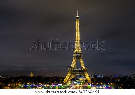 PARIS - DECEMBER 22: Eiffel Tower brightly illuminated at dusk on December 22, 2014 in Paris. The Eiffel tower is the most visited monument of France. - stock photo