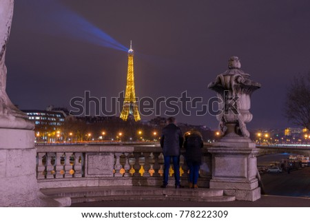 PARIS - December 10 2017: Eiffel Tower with night illumination and lampposts on Alexander the Third bridge  in Paris, France. Alexander the Third bridge is popular touristic site in Paris
