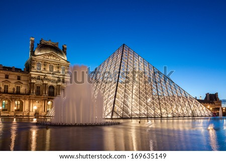 PARIS - DECEMBER 26, 2013: Louvre Museum at dusk on December 26, 2013 in Paris. The Louvre Museum is the most famous and most visited museum of the world with about 8 million visitors every year. - stock photo