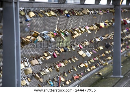 PARIS - DECEMBER 25: Love padlocks, a tradition of the romantic Paris, representing eternal love of the couples, who lock padlocks on a bridge over the Seine river in Paris, France, December 25, 2014.