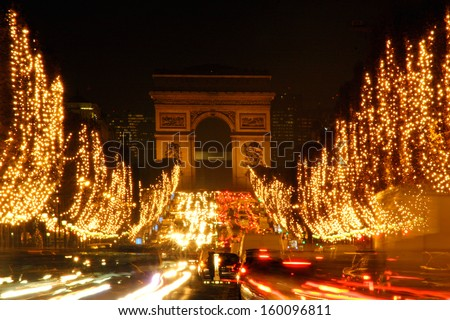 PARIS - DECEMBER 7 : Paris at night on Champs-Elysees in front of Arc de Triomphe  Dec 7, 2005 in Paris, one of  the most visited monument in France.  - stock photo
