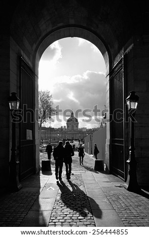 PARIS - DECEMBER 2,: Silhouettes of tourists walking through an arch at the Louvre towards the Pont Des Arts over the Seine River in Paris, France, on December 2, 2011. - stock photo