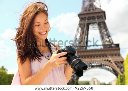 Paris Eiffel Tower tourist with camera taking pictures in front of the Eiffel tower, Paris, France. Young photographer woman in her 20s. - stock photo