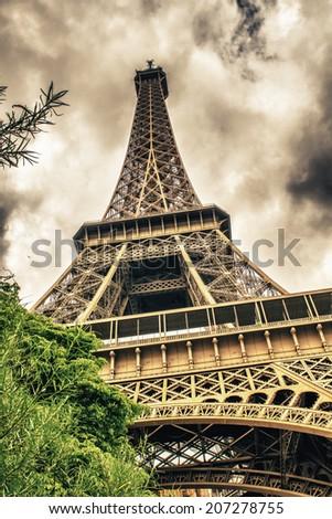 Paris. Eiffel Tower with summer trees on a cloudy sky. - stock photo