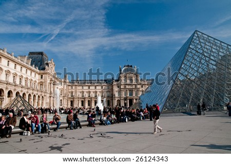 PARIS - FEBRUARY 28: a crowd enjoys the view and the weather at the glass pyramid in the louvre in Paris on February 28, 2009 in Paris. - stock photo