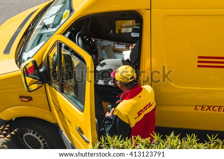 PARIS, FRANCE - APR 21, 2016: Courier enters DHL yellow delivery van after delivering the on time delivering package parcel - stock photo
