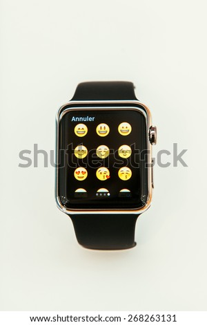 PARIS, FRANCE - APR 10, 2015: New wearable computer Apple Watch smartwatch displaying the new emoji faces. Apple Watch has fitness tracking & health-oriented &  integration with iOS Apple products - stock photo