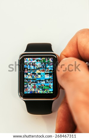 PARIS, FRANCE - APR 10, 2015: New wearable computer Apple Watch smartwatch displaying the new Photo App. Apple Watch has fitness tracking and health-oriented capabilities with iOS products - stock photo