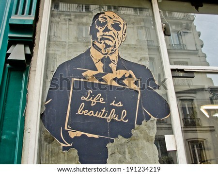 PARIS, FRANCE - APRIL 27, 2013: Anonymous old billboard with a man holding a sign saying life is beautiful  as seen on on a shop window in Paris on April 27, 2013 - stock photo