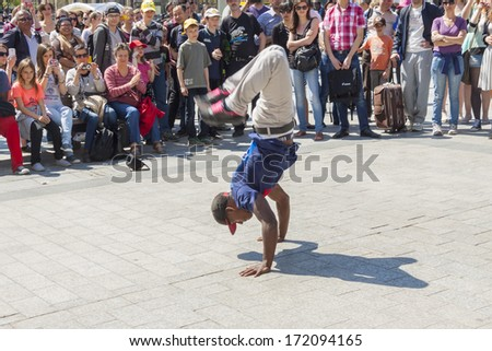 PARIS, FRANCE -  APRIL 25:B-boy doing some breakdance moves in front a street crowd, at Arch of Triumph on april 25, 2013 in Paris. Its popular form of earnings in big cities. - stock photo