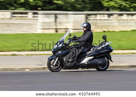 PARIS, FRANCE - APRIL 15, 2014: Business man travelling to work on a scooter in Paris, France, on April 15, 2014