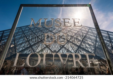 PARIS, FRANCE- APRIL 14, 2013: Musee Du Louvre Sign in front of The large glass pyramid at the Louvre Museum.The Louvre Museum is one of the cultural heritages of the world - stock photo