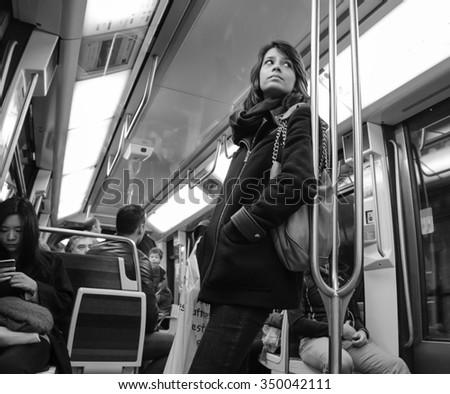 PARIS, FRANCE - APRIL 6, 2015: People in train of Line 1 in Parisian Metro. The Paris Metropolitain is serving over 1.5 billion passengers per year. - stock photo