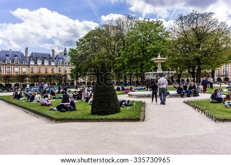 PARIS, FRANCE - APRIL 12, 2015: People relaxing on green lawns of famous Place des Vosges - oldest planned square in Paris, in Marais district. Place des Vosges was built by Henri IV from 1605 to 1612