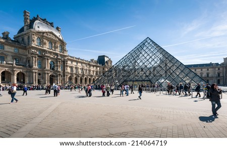 PARIS, FRANCE - APRIL 14, 2013: Tourists in the Louvre's central courtyards with the Louvre pyramid and palace. The Louvre is the world's most visited museum - stock photo