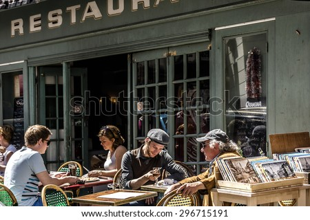 PARIS, FRANCE - APRIL 23, 2015: View of typical cafe in Paris. Montmartre area is most popular destinations in Paris, has lots of cozy cafes, restaurants, bistros, night clubs and artistic studios. - stock photo