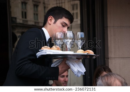 PARIS, FRANCE - APRIL 20, 2014 : Waiter serving customers at traditional outdoor Parisian cafe in center city. Street buildings are reflected in the glasses.