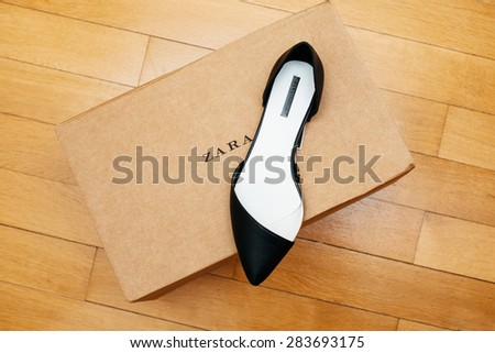 PARIS, FRANCE - APRIL 13, 2015: ZARA shoe placed on cardboard box in luxury retail shopping center with wooden parquet floor - stock photo