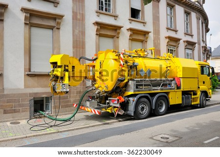 PARIS, FRANCE - AUG 26, 2013: Sewage or sewerage - truck on city street in working process to clean up sewerage overflows, cleaning pipelines and potential pollution issues from an modern building - stock photo