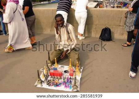 Paris, France August 18 2014. African immigrant offering souvenirs on a bridge over the Seine. Paris, France August 18 2014 - stock photo