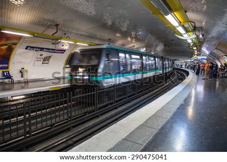 Paris, France - August 9, 2014: Barbes-Rochechouart. Parisian subway station with passengers and moving train, motion blur effect - stock photo