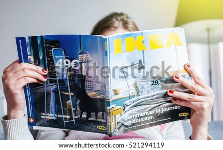 PARIS, FRANCE - AUGUST 24, 2014: Busy woman reading IKEA Catalogue before buying furniture for her new house. The catalogue is published annually by the Swedish home furnishing retailer