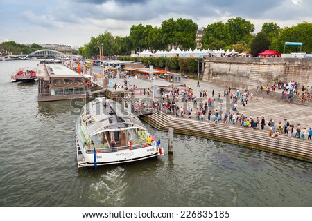 Paris, France - August 07, 2014: passenger touristic ship operated by Batobus Paris is moored to the pier near Eiffel Tower. People are waiting  of boarding in a long line - stock photo