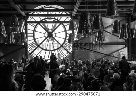 Paris, France - August 10, 2014: Restaurant with famous ancient clock window in Orsay Museum is full with visitors and personnel, black and white photo - stock photo
